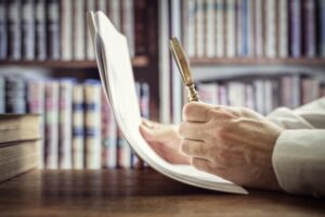 Businessman or attorney with magnifying glass reading documents